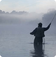 A lone fisherman, knee deep in water casts his line into the foggy waters.
