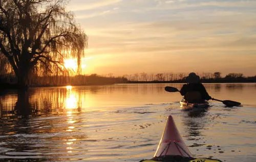 A sunset is reflected in the water as two kayakers enjoy the natural splendour of the Grand River