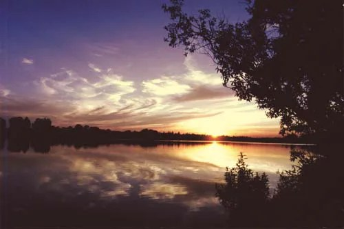 A beautiful sunset is reflected in a still lake; the sky awash with the beautiful dusky colours of the sunset.