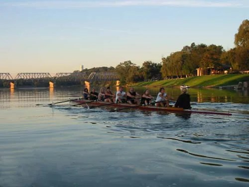 Rowers practice their craft at sunset on the Grand River