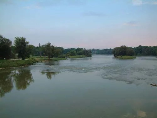 The hues of dusk's purple and blue are reflected in the gentle waves of the Grand River