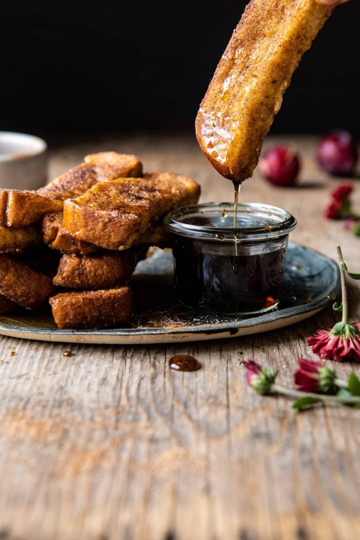 side angled photo of Cinnamon Sugar French Toast Sticks being dipped into maple syurp