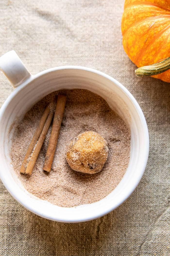 Pumpkin Butter Chocolate Chip Cookie dough ball sitting in cinnamon sugar