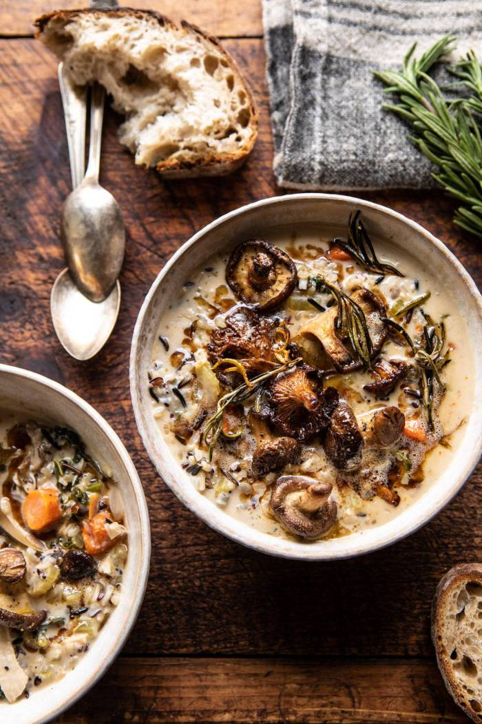 overhead photo of Creamy Wild Rice Chicken Soup with Roasted Mushrooms with bread and spoons on table next to soup bowls