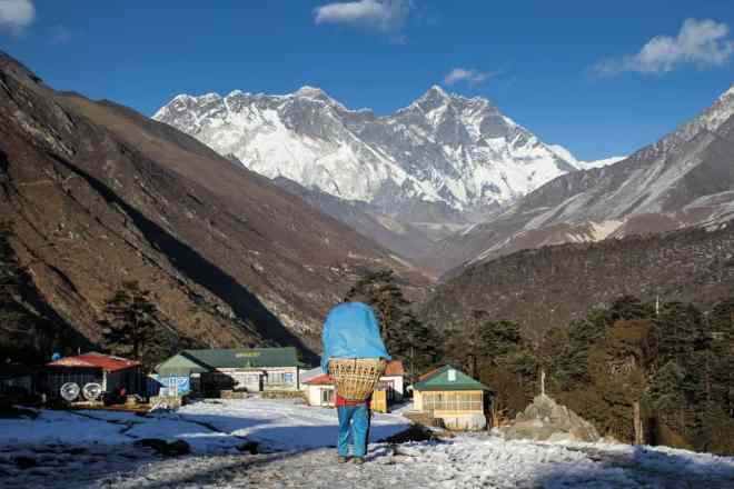 A porter passing through Tengboche with Everest in the background (on the left).