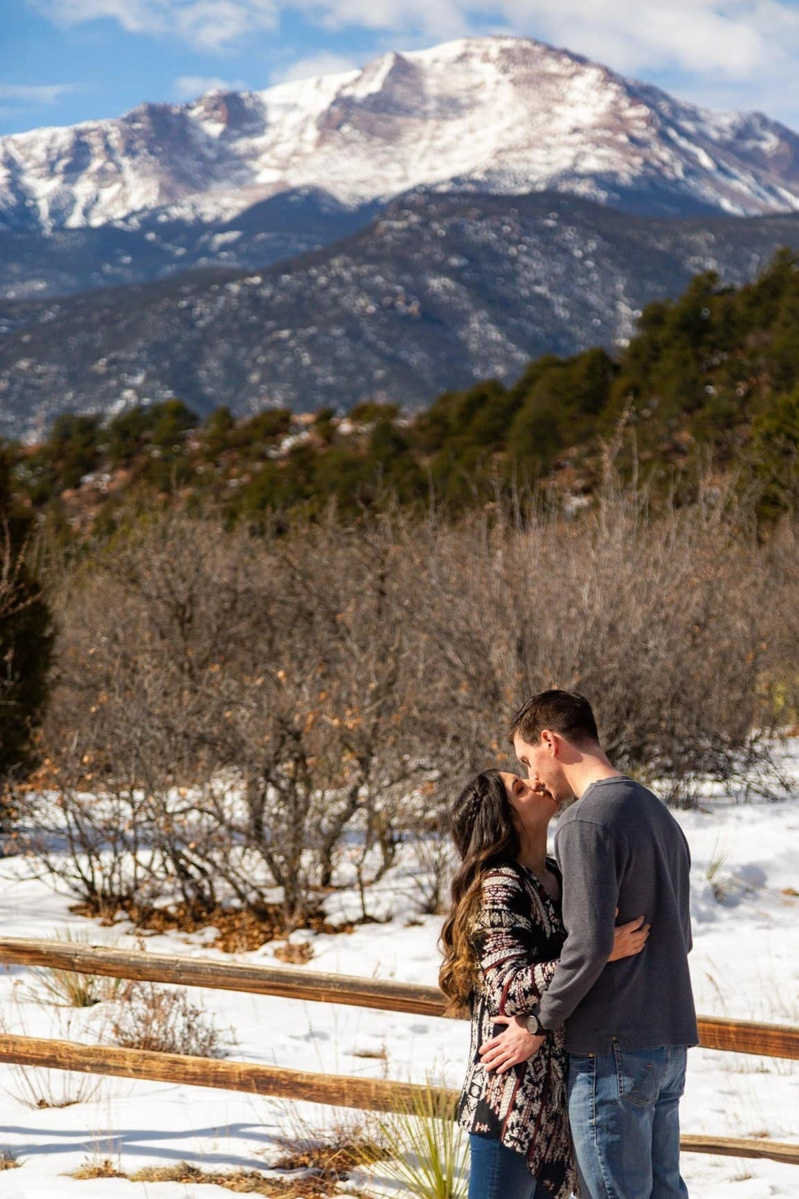 Couple embraces while Pikes Peak looks on in the background. Garden of the Gods is a great place for adventure with the one you love most