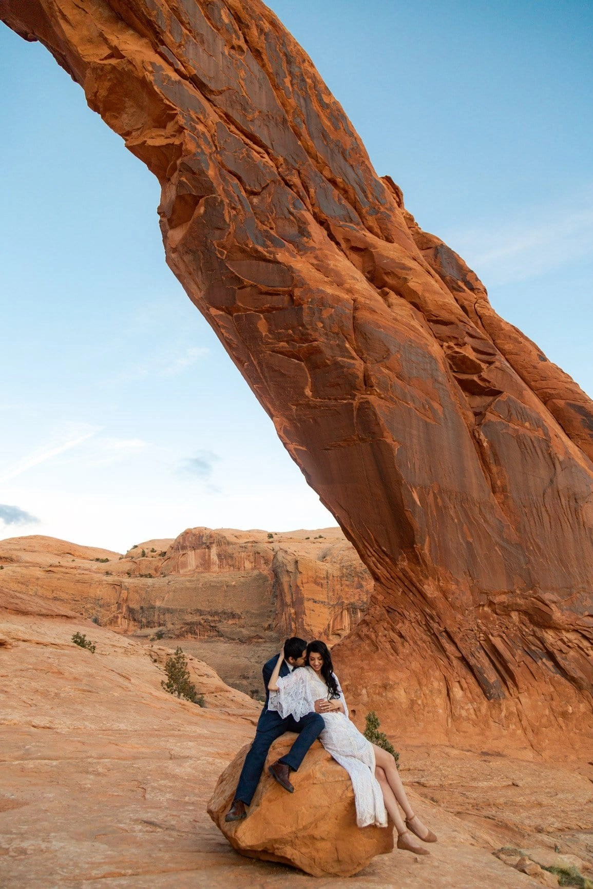 eloping couple cuddling under the Corona Arch in Moab, Utah