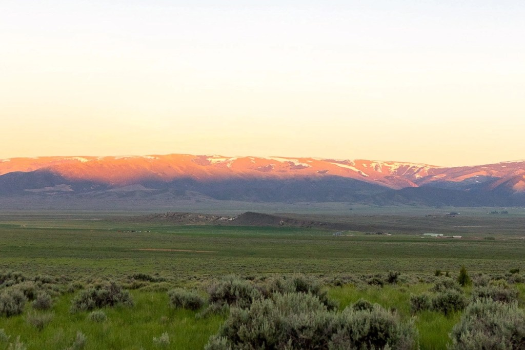 the sunset over a mountain range in idaho