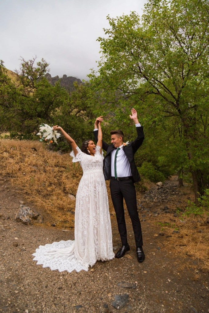couple excitedly celebrates their love by holding hands and reaching their arms out wide