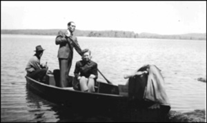 Man in suit paddling a boat with two others in it