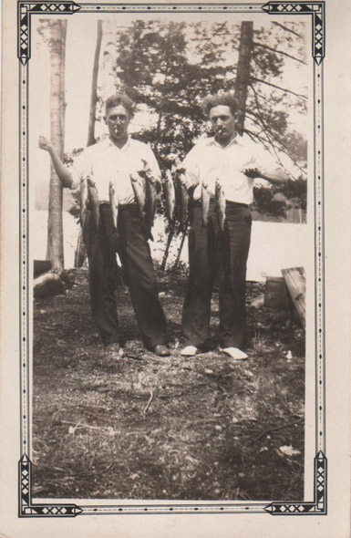 Men posing with fish on a string