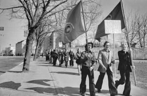 19740501 . Vappumarssijoita Hämeentiellä. Nuoret miehet kantavat kulkueen edessä järjestölippuja ja kylttiä, jossa teksti: Hermannin sosialistiset nuoret ry.
