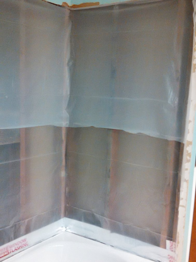 Add flashing and plastic sheeting before tiling a shower