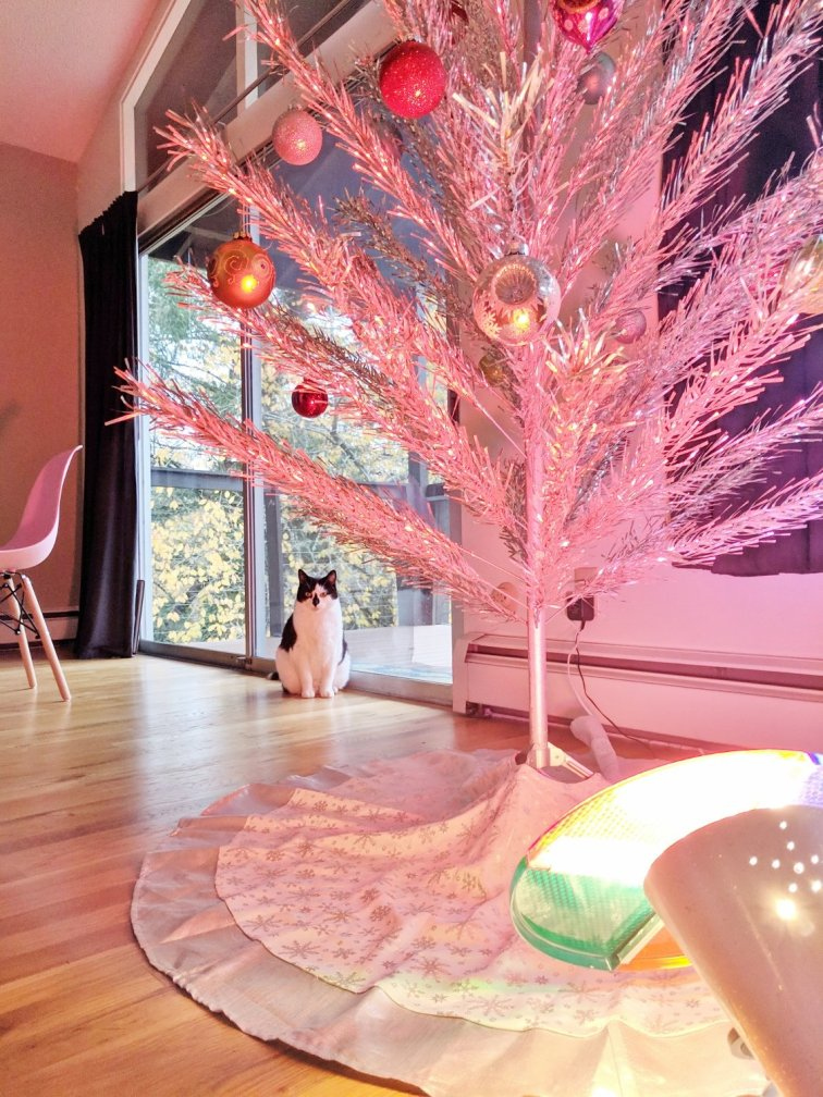 Decorate an aluminum Christmas tree with colorful bulbs and light it up with a color wheel