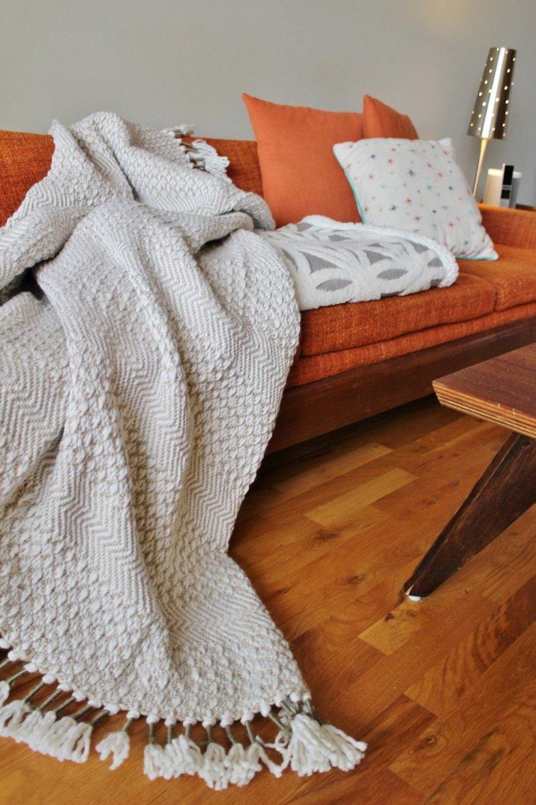 Modern neutral throw blankets on mid-century sofa