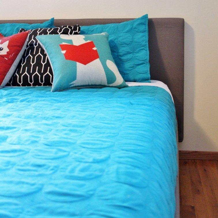 Turquoise bedspread in mid-century modern bedroom