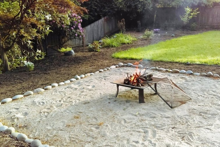Backyard with sandy fire pit area, mulch and plants