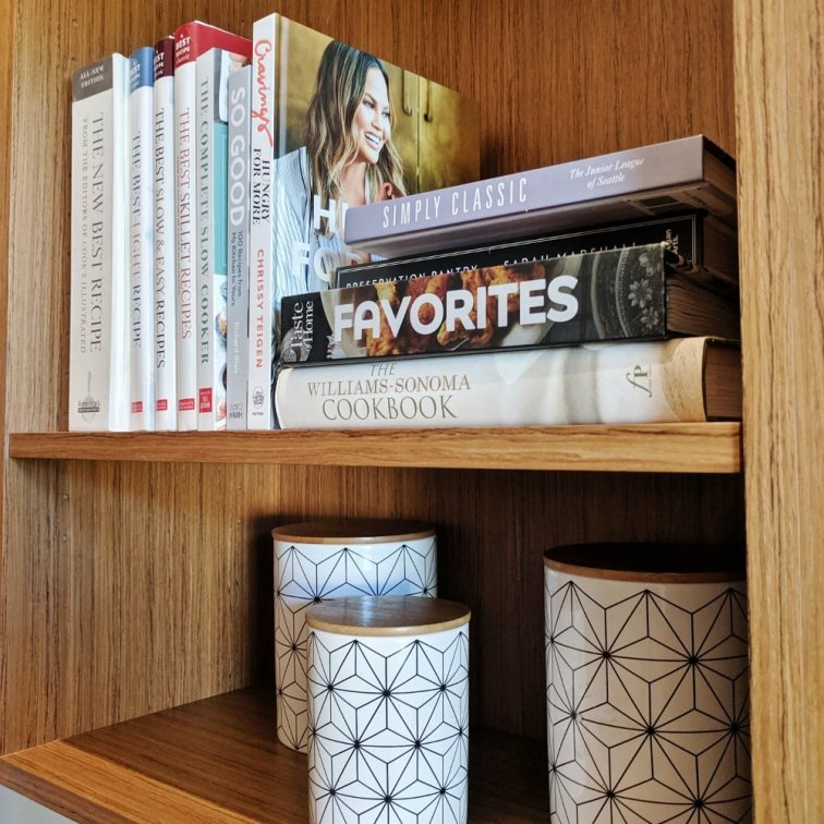 Cookbook display with modern canisters on pretty shelves