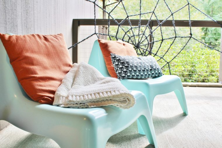 Midcentury modern chairs and Halloween decor with spider web