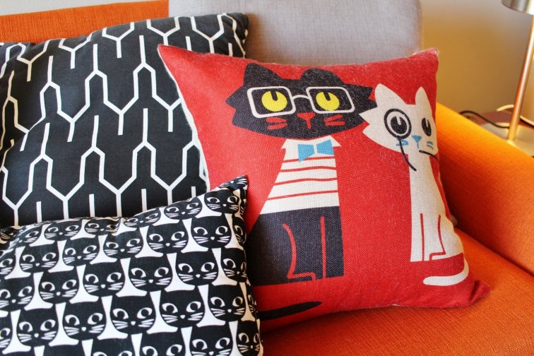 Mod atomic kitty throw pillows on a mid-century couch