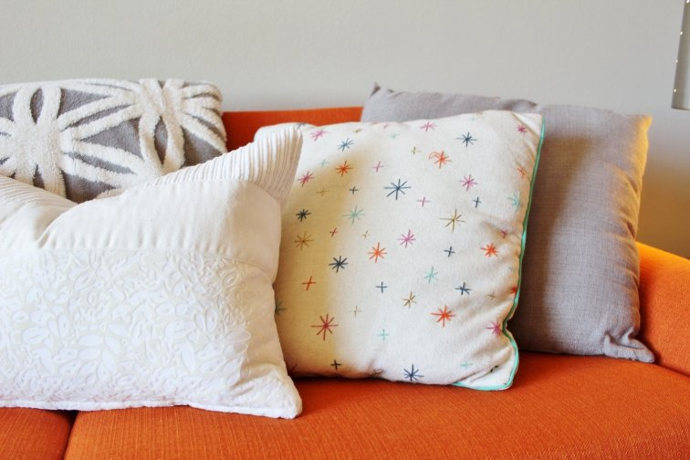 Light and bright starburst pillows look great on an orange sofa