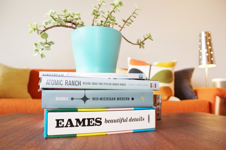 Mid-century modern coffee table books displayed in retro living room