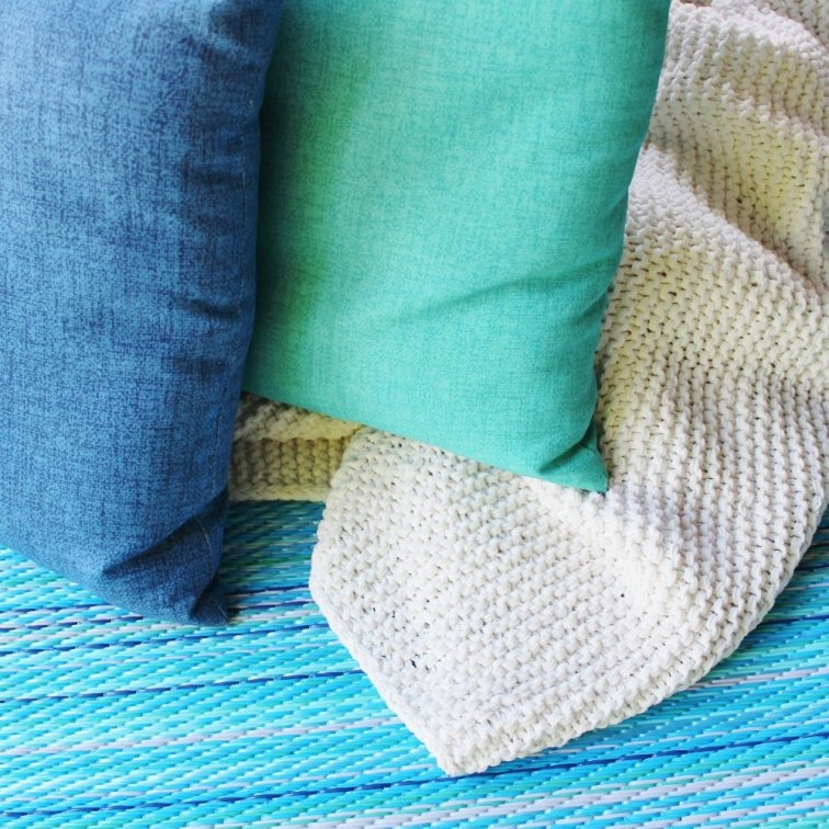 Outdoor pillows and rug in shades of blue