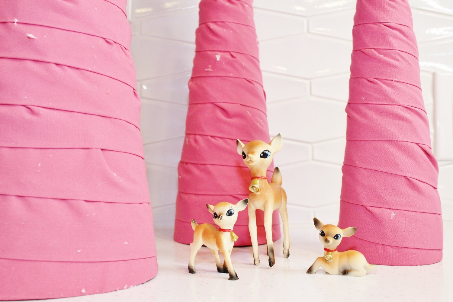 Deer figurines surrounded by pink fabric cone tree Christmas decor