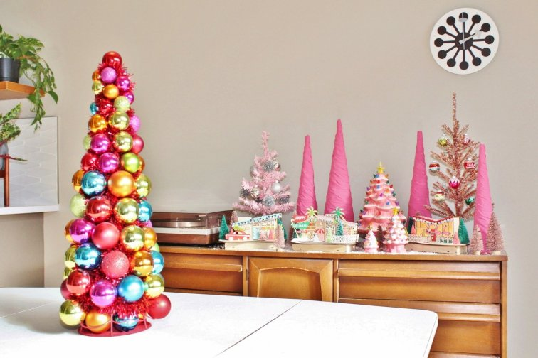 Tabletop pink Christmas trees on display with mid-century Christmas village
