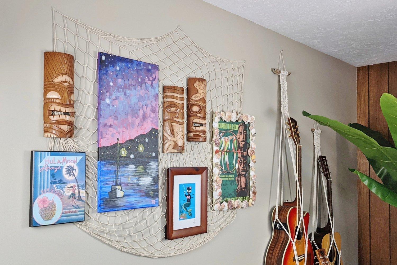 Tiki bar gallery wall with tropical art, tiki masks and guitars