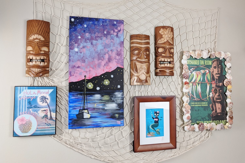 Tiki bar gallery wall with fishing net, tropical art and tiki masks