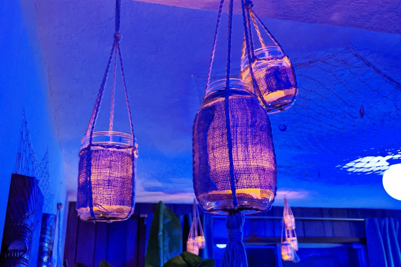 Amber glowing DIY lanterns under blue lighting in tiki bar