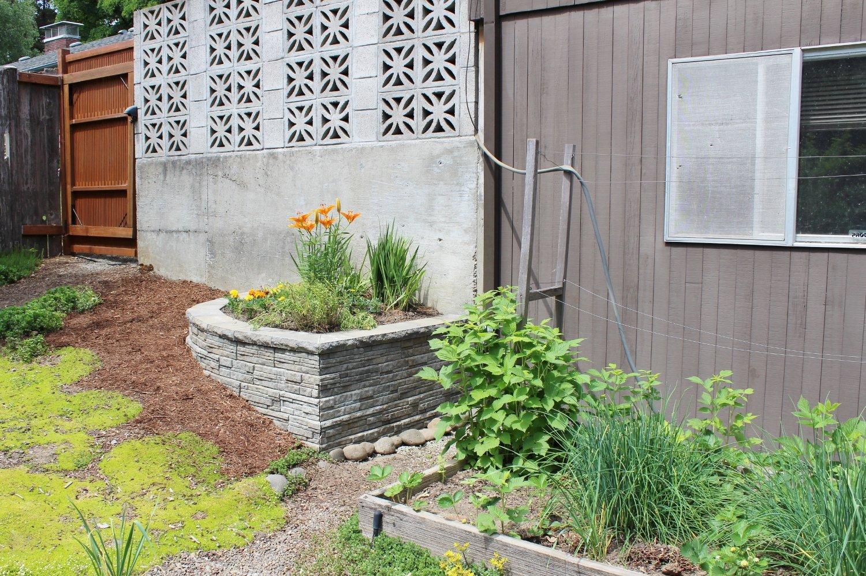 Mid-century modern retaining wall planter and breeze block in backyard landscape