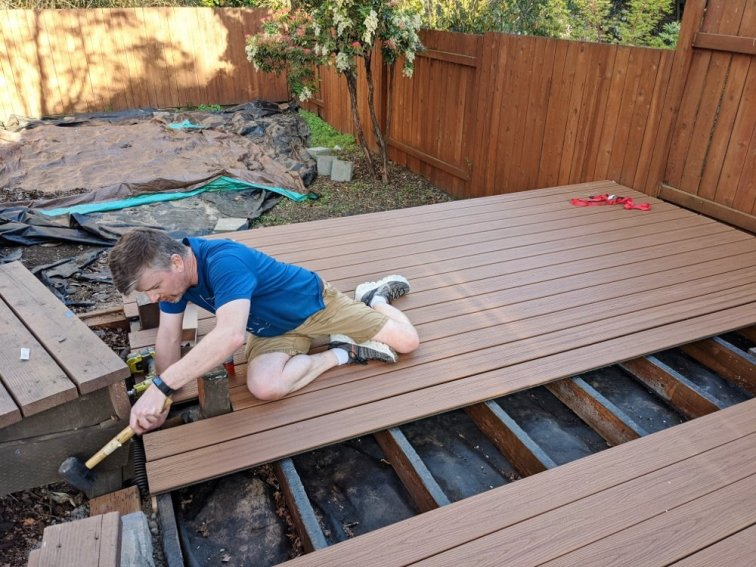Tapping Trex composite board into place while building deck