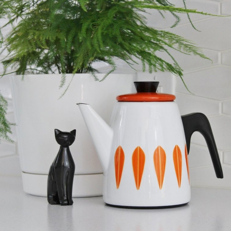 Cathrineholm orange and white coffee pot with houseplant and mid-century cat