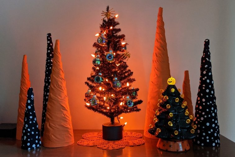 Halloween cone trees lit up with orange glow at dusk