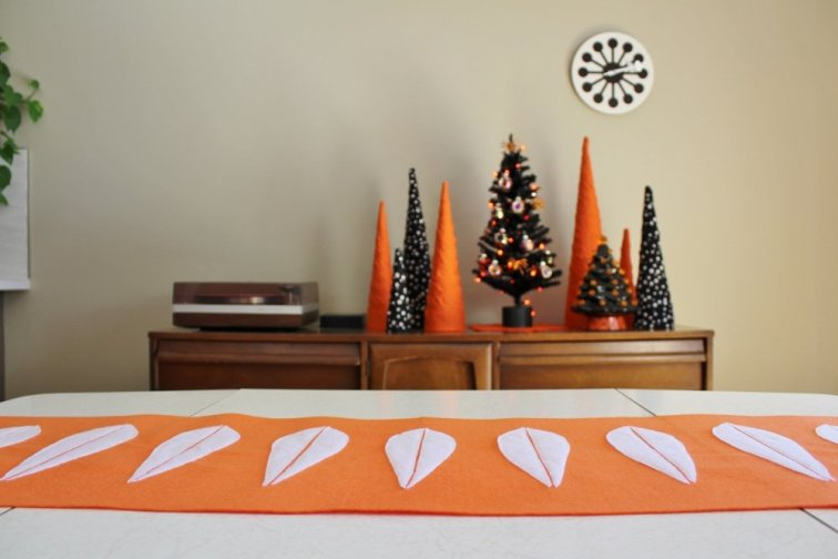 Orange and white lotus table runner with Halloween trees in the background