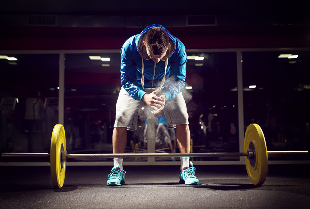Cross fit weightlifter preparing for training. Shallow depth of