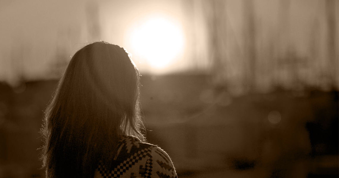 sexual abuse in marriage- a woman stands looking towards the sun
