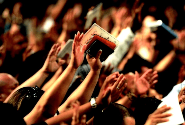 Hillsong bushfire appeal- image of hands raised in a church