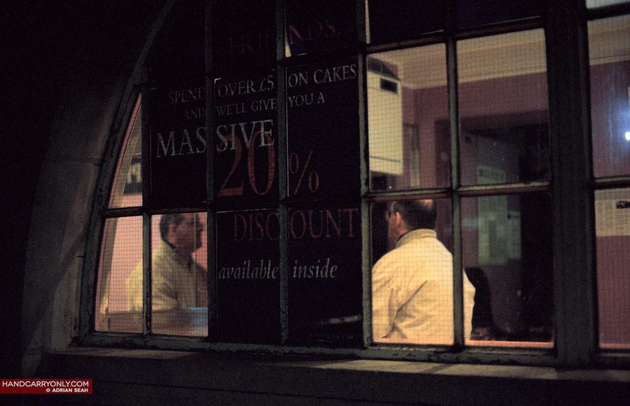 man in window staring at mirror