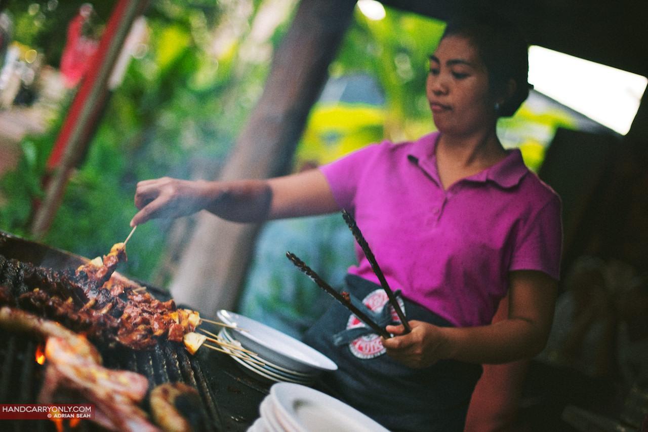 Girl BBQ-ing ribs at outdoor grill bali
