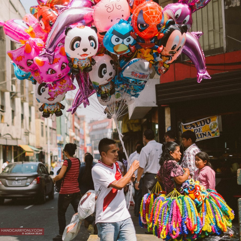 A balloon seller with his colourful wares on the streets of Lima Peru