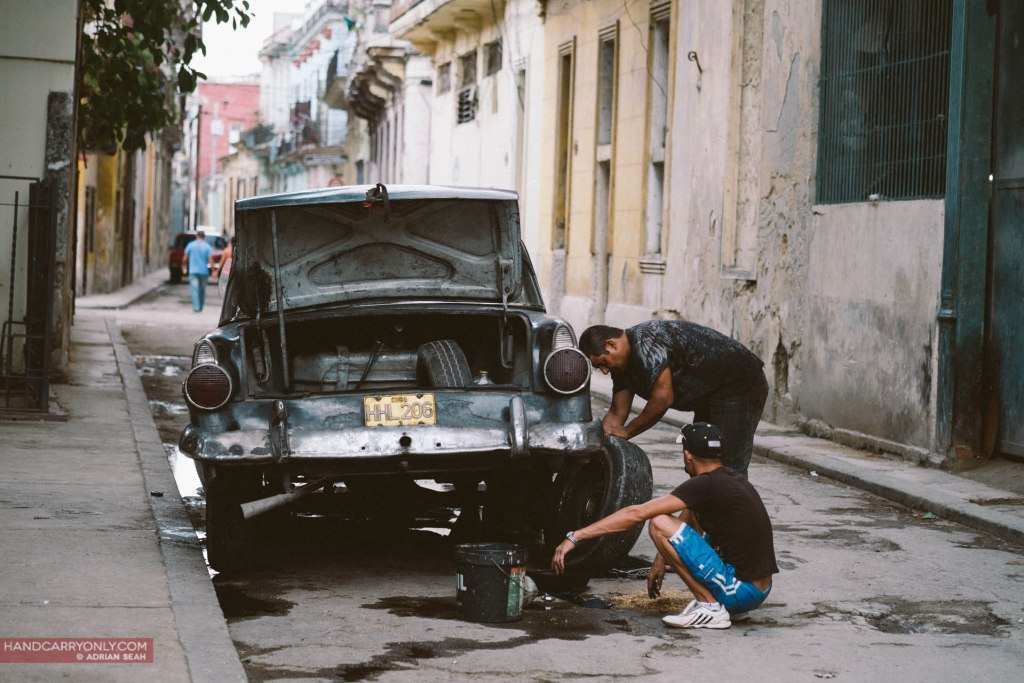 two men fixing an old classic car in havana cuba