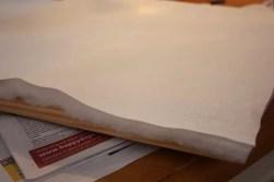 Lägg på vadd och linnetyg (lägg till ca 10 cm utanför ramen), häfta fast tyget på baksidan