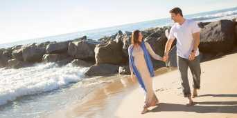 parents pregnant walking beach