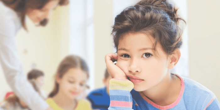 Girl looking unhappy at school in post about how to tell if school is stressing your child