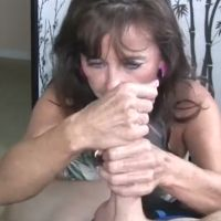 Naughty granny uses both hands to jerk him off