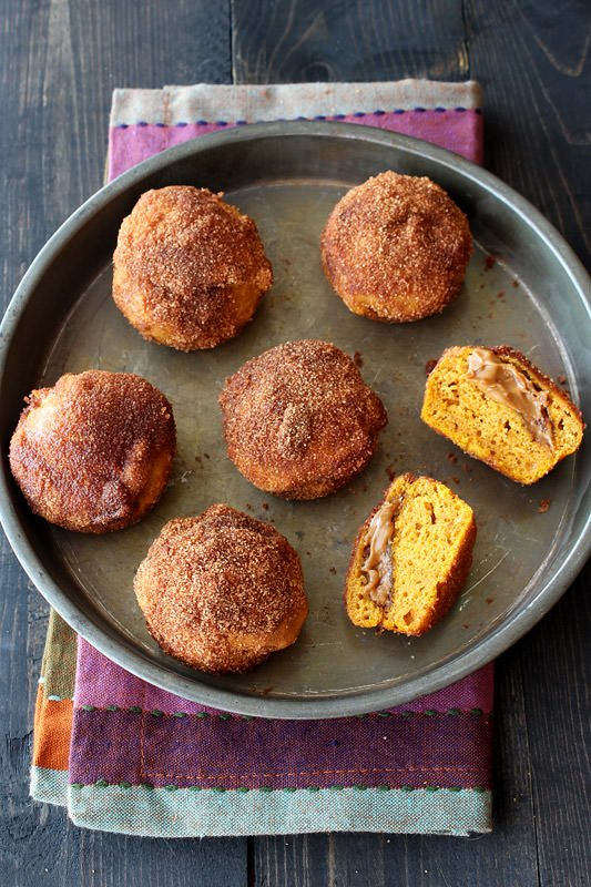 Biscoff Stuffed Pumpkin Mini Muffins are coated with cinnamon sugar and perfect for fall! From HandletheHeat.com