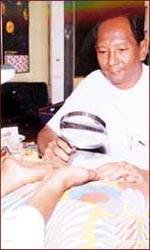 Palmist Theikpan Myint Oo reads hands in Myanmar.
